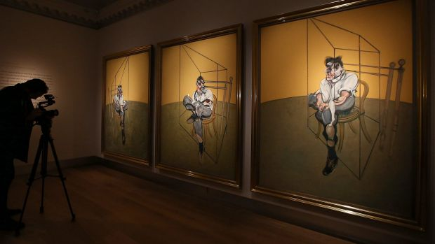 A cameraman films Francis Bacon's 'Three Studies of Lucien Freud' on display at Christie's on October 14, 2013 in ...