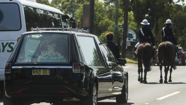 A pair of mounted police lead the hearse away.