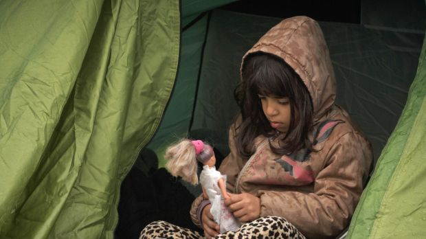 A girl plays with a doll at the northern Greek border station of Idomeni.