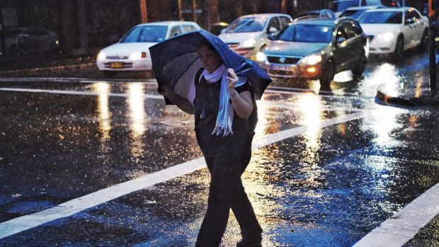 A woman battles a soggy morning commute in Darlinghurst on Tuesday.