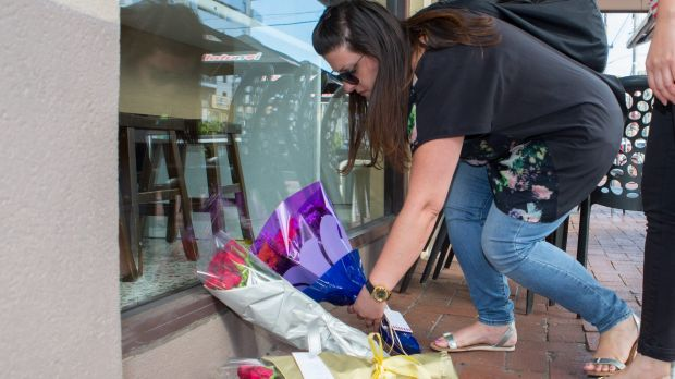 A woman lays flowers at Joseph Acquaro's Gelobar restaurant on Tuesday.
