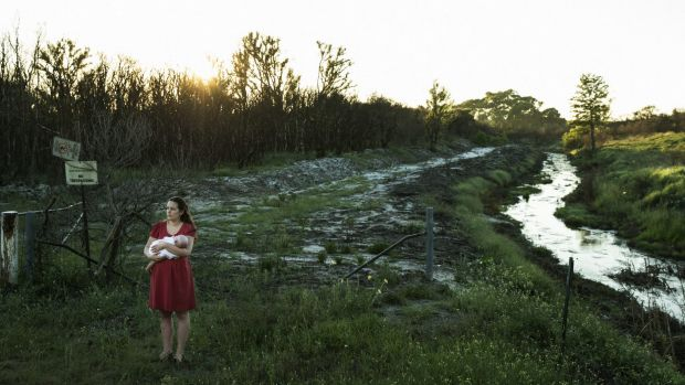 Samantha Kelly holds her baby William beside one of the drains running from the Williamtown RAAF base near Newcastle.