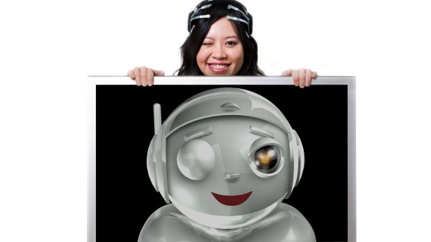 Le wearing the original EPOC headset that senses her smile and wink, causing a computer-generated cartoon robot to ...