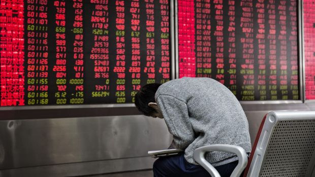 A man reads in front of an electronic board displaying share prices at a securities brokerage in Beijing.