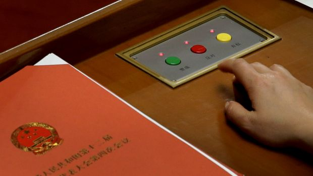 A delegate prepares to press buttons to vote on the draft resolutions during the closing session of the annual National ...