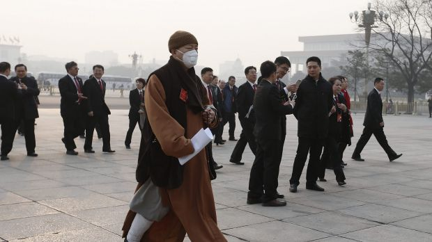 A delegate wearing a mask walks to the Great Hall of the People during severe pollution before the closing session of ...