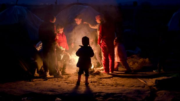 Migrants stand around a fire at the northern Greek border point of Idomeni, Greece. German Chancellor Angela Merkel is ...