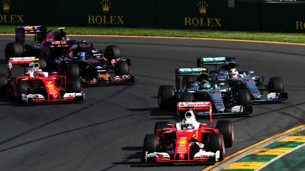 Sebastian Vettel squeezes through the McLaren front row to take the lead.