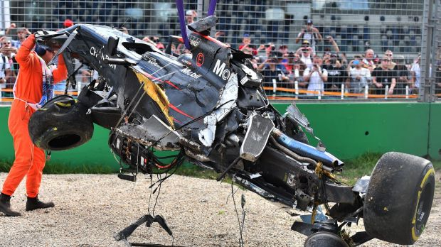 A track official assists the removal of McLaren driver Fernando Alonso's car.