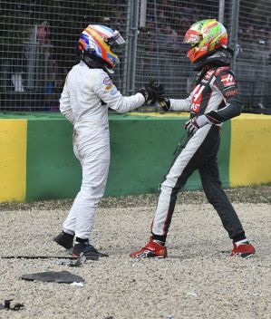 McLaren driver Fernando Alonso, left, and Haas driver Esteban Gutierrez shake hands following the crash.