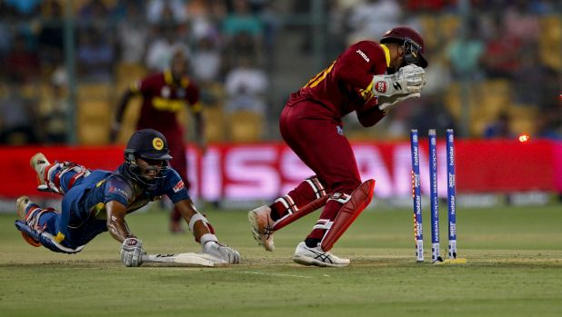Denesh Ramdin breaks the stumps to run out Sri Lanka's Dinesh Chandimal in Bangalore.
