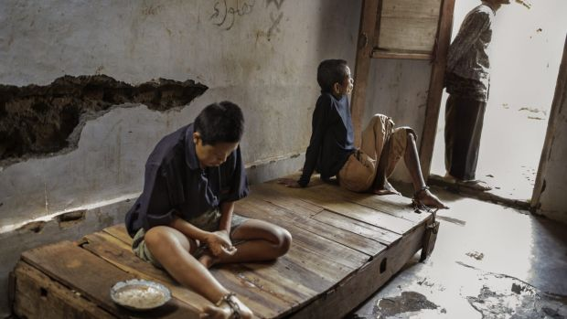 Two residents at the Bina Lestari healing centre in Brebes, Central Java, are chained to a wooden platform bed while an ...