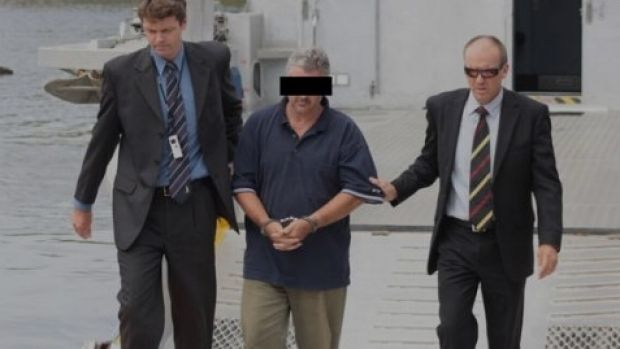 Steven Fennell escorted by detectives after his arrest over the murder of Liselotte Watson on Macleay Island.