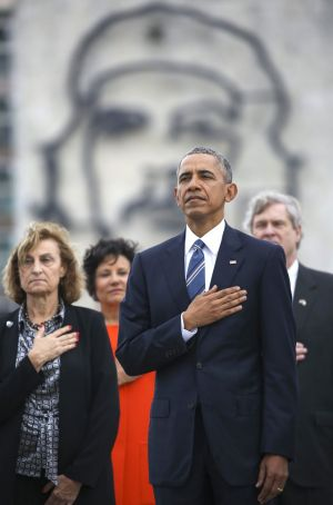US President Barack Obama listens to the US national anthem in front of a a monument depicting Cuba's revolution hero ...