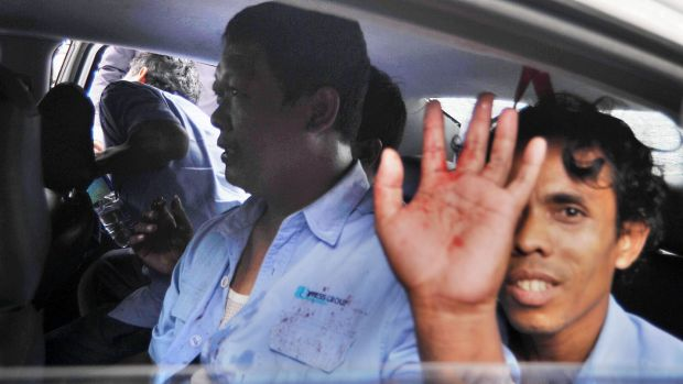 A Jakarta taxi driver has blood on his shirt after being struck by protesters against the Uber public transport app.