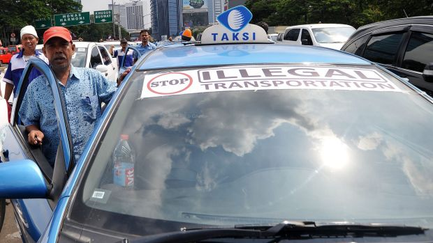 Taxi driver A.S. Sudrajat stands beside his vehicle during mass strikes against app-based competitors Uber and GrabTaxi ...