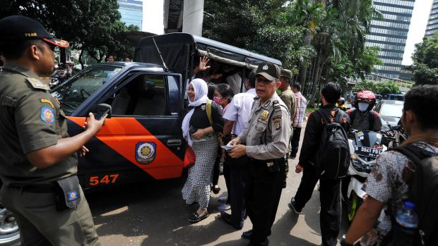 Citizens evacuated by police during the mass  unrest over public transport in Jakarta.