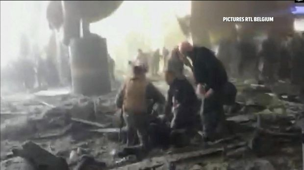 People receive treatment in the debris strewn terminal at Brussels Airport after explosions on Tuesday.
