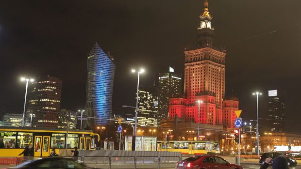 The Palace of Culture, right, the tallest building in the Polish capital, is lit in the colors of the Belgian flag in ...