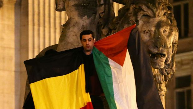 A man waves a Belgian and Palestinian flag as a mark of solidarity at the Place de la Bourse in Brussels on Tuesday.