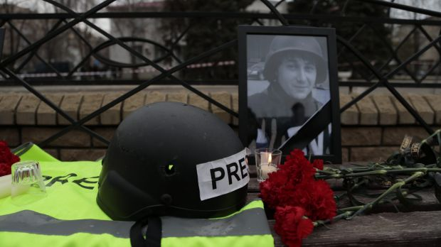 Portrait of killed Russian journalist Anton Voloshin, with flowers, outside the court in Donetsk on Tuesday.
