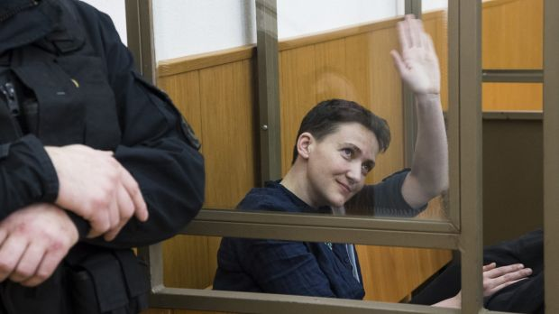 Ukrainian pilot Nadezhda Savchenko waves from a glass cage in court, in Donetsk on Tuesday.