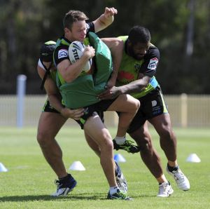 Raiders halfback Sam Williams gets tackled by two teammates at training this week.