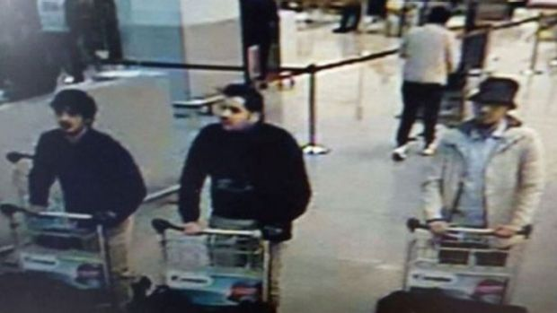 "A hunt is under way for a ""man in white"", one of three men filmed pushing luggage trolleys in Zaventem Airport before ..."