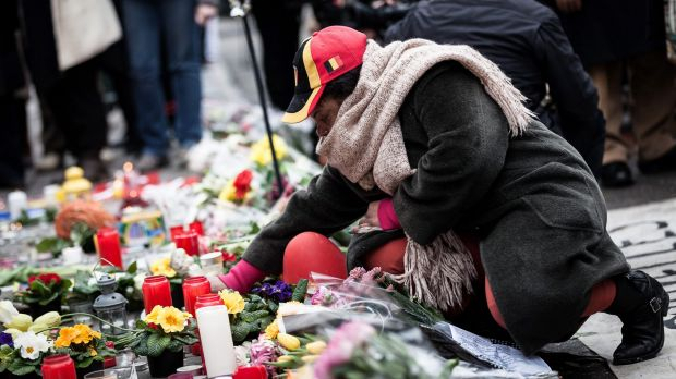 A woman lights a candle at a memorial for victims of attacks in Brussels on Wednesday, March 23.