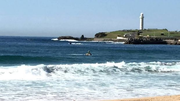 Surf life saving divers search the seas for a missing swimmer, towed by a colleague on a jetski at North Wollongong.