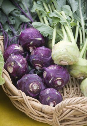 A basket of fresh organic purple and white kohlrabi on display at a local farmer's market.