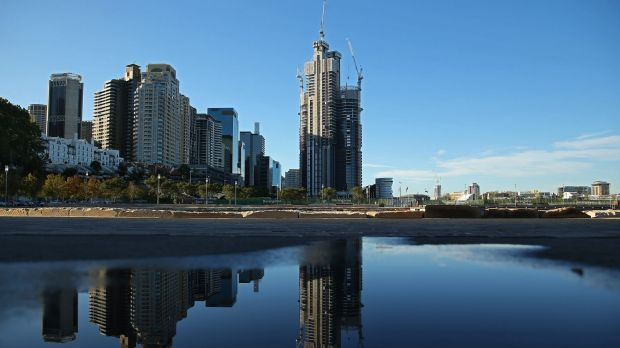 Buildings under construction at Lend Lease Group's Barangaroo redevelopment, center, are reflected in a puddle in Sydney.