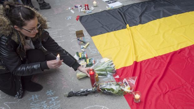 A woman places a candle next to a Belgian national flag during a vigil in Montreal on Wednesday.