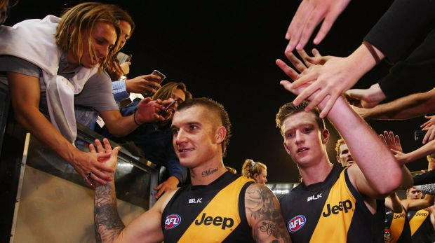 Well done: Dustin Martin celebrates with fans as he leaves the ground after the win over Carlton.