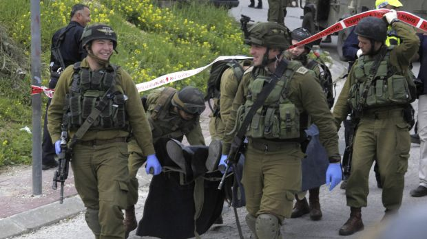 Israeli soldiers carry the body of one of two Palestinian who were killed after a stabbing attack in Hebron, on the ...
