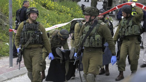 Israeli soldiers carry the body of Abdel Fattah al-Sharif from the scene of the incident in the Israeli-occupied West ...