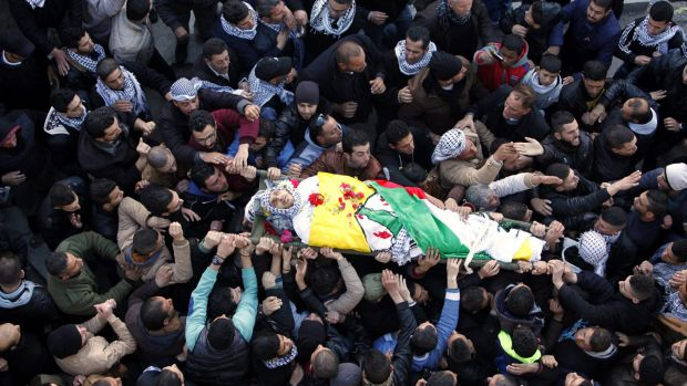 Palestinians carry the body of Ali Taqatqah, 19, on Sunday. The 19-year-old attacked Israeli soldiers with a knife and ...