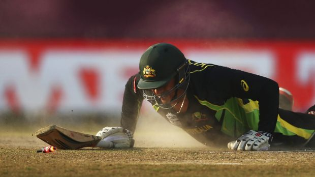 Sliding in: Usman Khawaja is run out by New Zealand's Grant Elliott in Dharamsala.