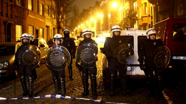 Police officers patrol after raids in which several people, including Paris attacks suspect Salah Abdeslam, were ...