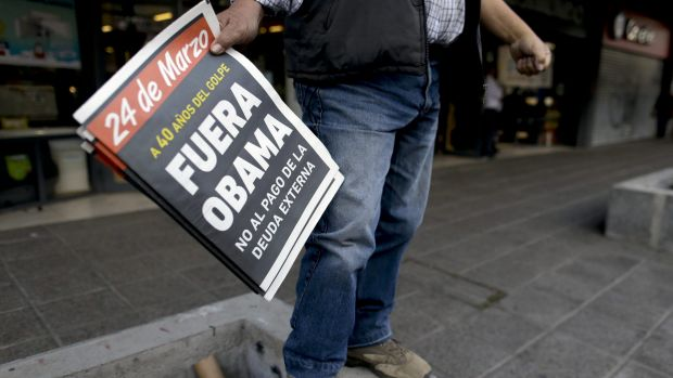 """A protester holds a newspaper saying: """"Get out Obama. 40 years since the coup. No to the payment of the external debt,"""" ..."""