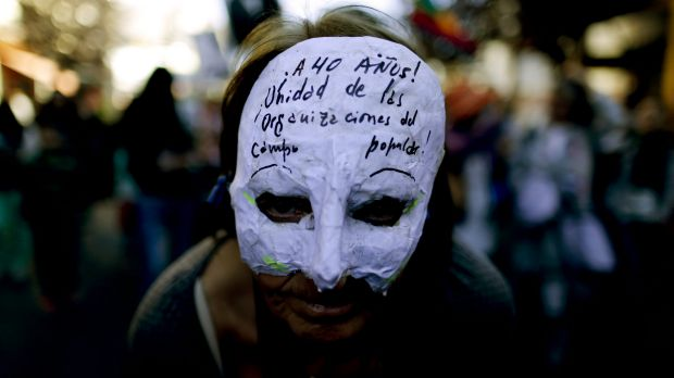 """A demonstrator wears a mask that reads in Spanish: """"At 40 years! Unity of people's organisations"""" in Bariloche, Argentina."""