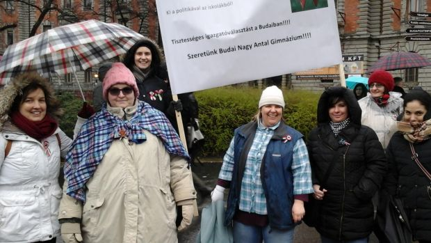 Near the Iron Curtain memorial, Budapest teachers wear check in protest at the state of Hungarian education.