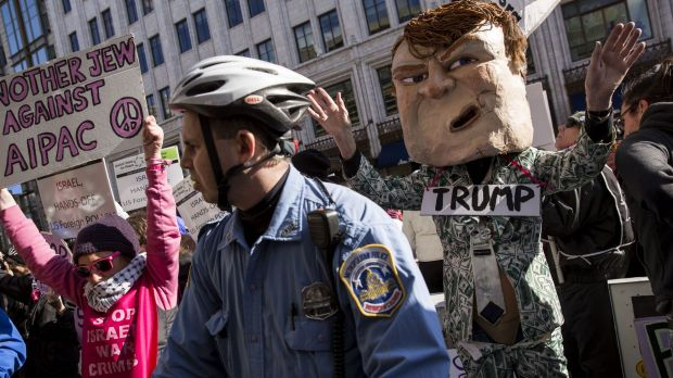 A police officer watches as protesters demonstrate against Donald Trump outside the American Israeli Public Affairs ...