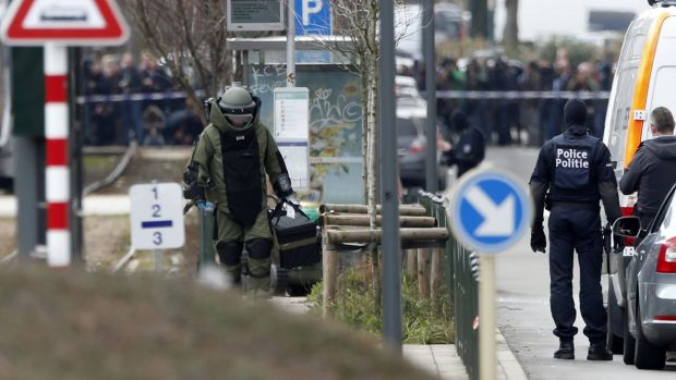 A member of emergency services wearing protective clothing investigates the area around a tram station in Schaerbeek, ...