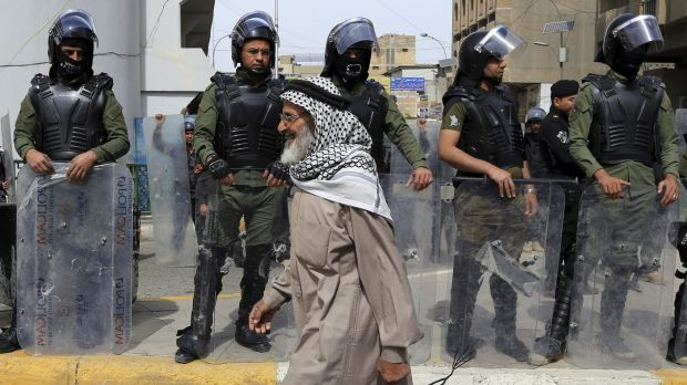 A protester passes riot police guarding the Green Zone.