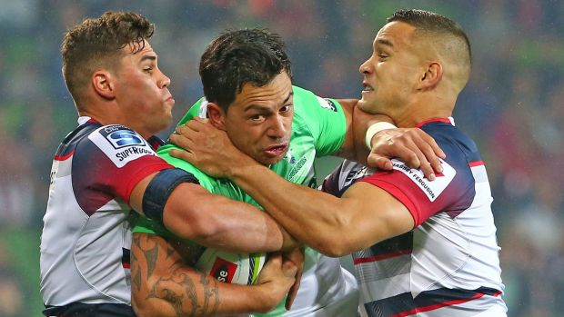 Rob Thompson of the Highlanders is tackled by Tom English and Tamati Ellison of the Rebels.