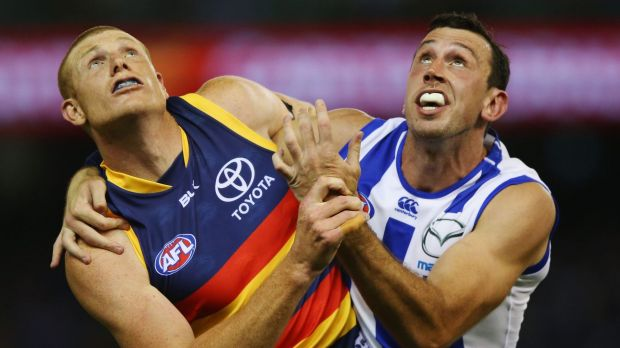 Sam Jacobs of the Crows and Todd Goldstein of the Kangaroos have eyes for nothing but the ball.