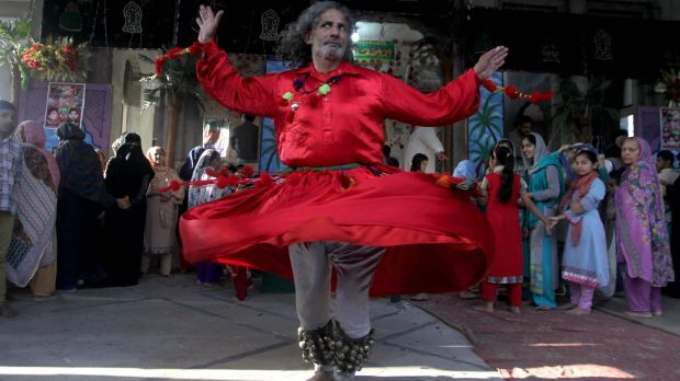 A Muslim devotee dances at the shrine of Shah Hussain, a poet also regarded as a Sufi saint, during a festival to ...