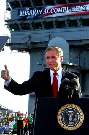 "George W. Bush flashes a ""thumbs-up"" after declaring the end of major combat in Iraq on board the aircraft carrier USS ..."