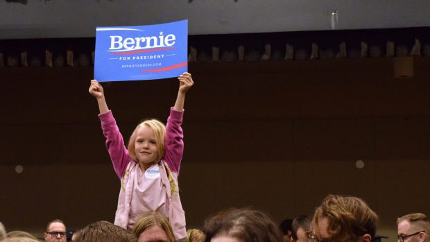"""A five-year-old holds up a """"Bernie Sanders for President"""" sign while sitting on her father's shoulders at the Juneau ..."""